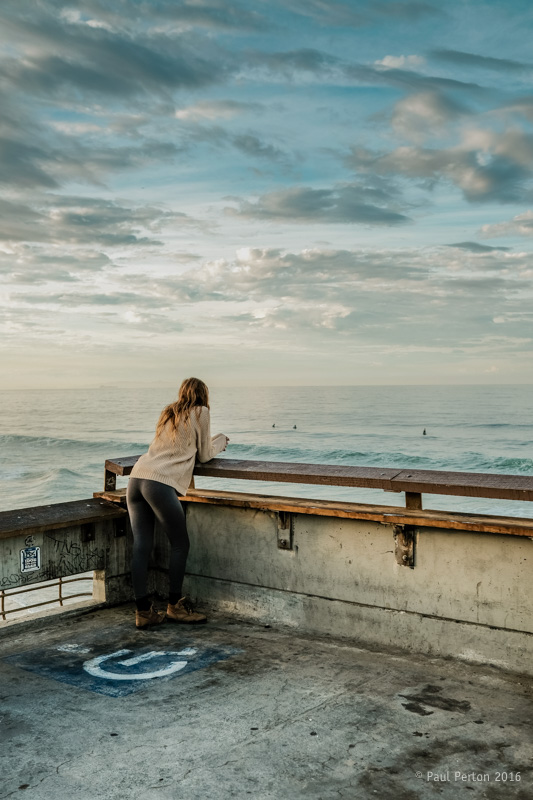 A portrait of a young woman watching surfers follows the rule of thirds
