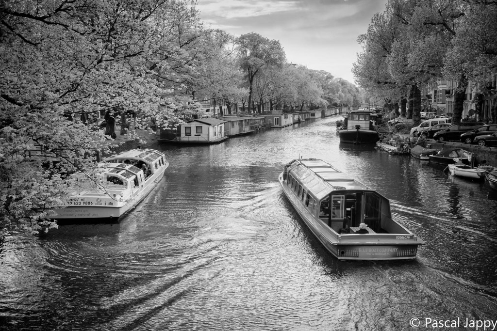 Canl boats and tourist barges on Pinsesgracht canal in Amsterdam