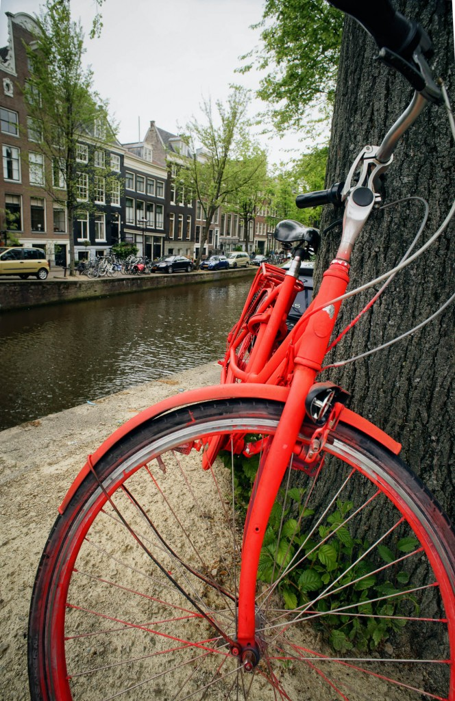 A bicycle painted bright orange in Amsterdam by a canal