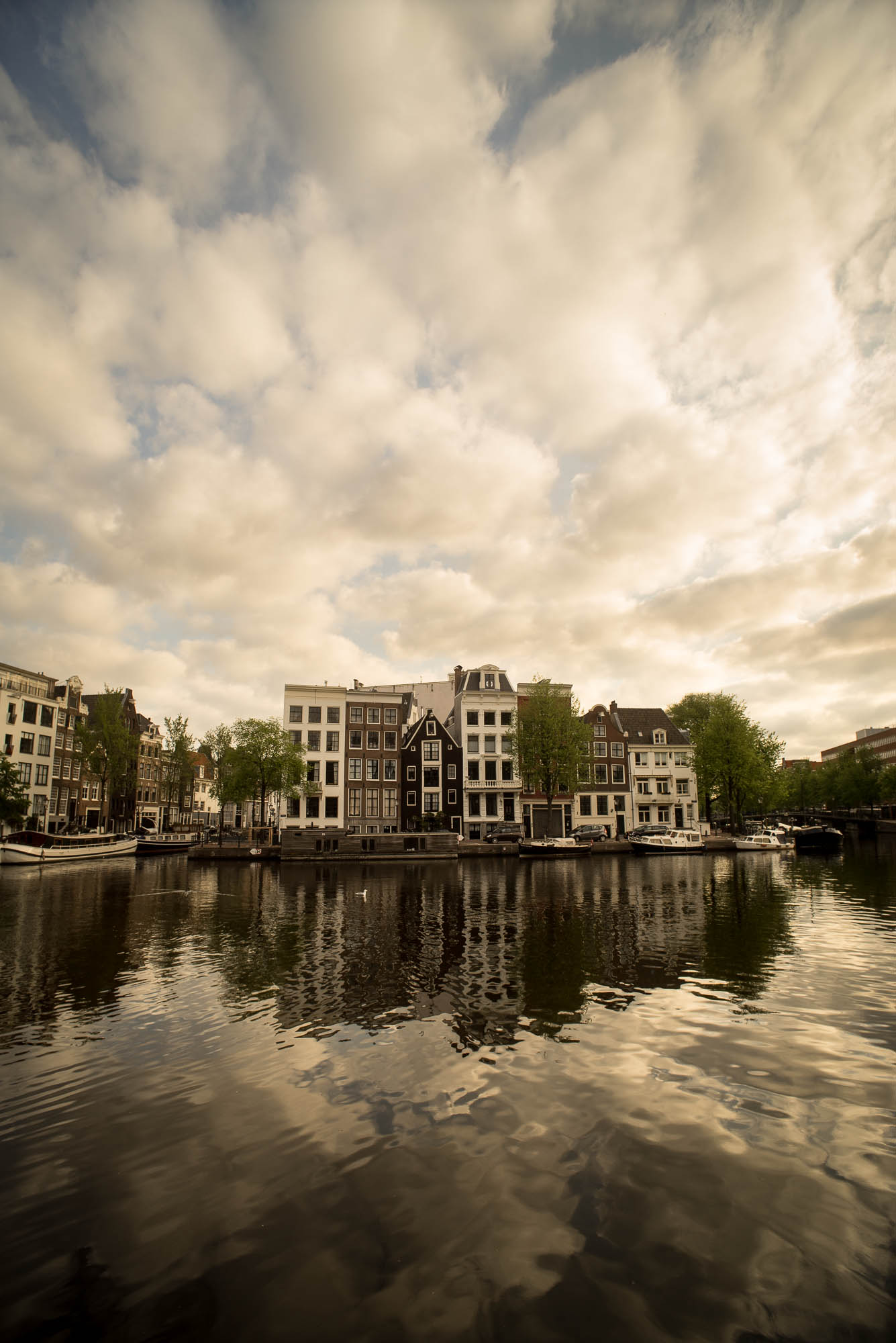 Houses reflections in the Amstel river on a spectacular morning sun, in Amsterdam, Holland