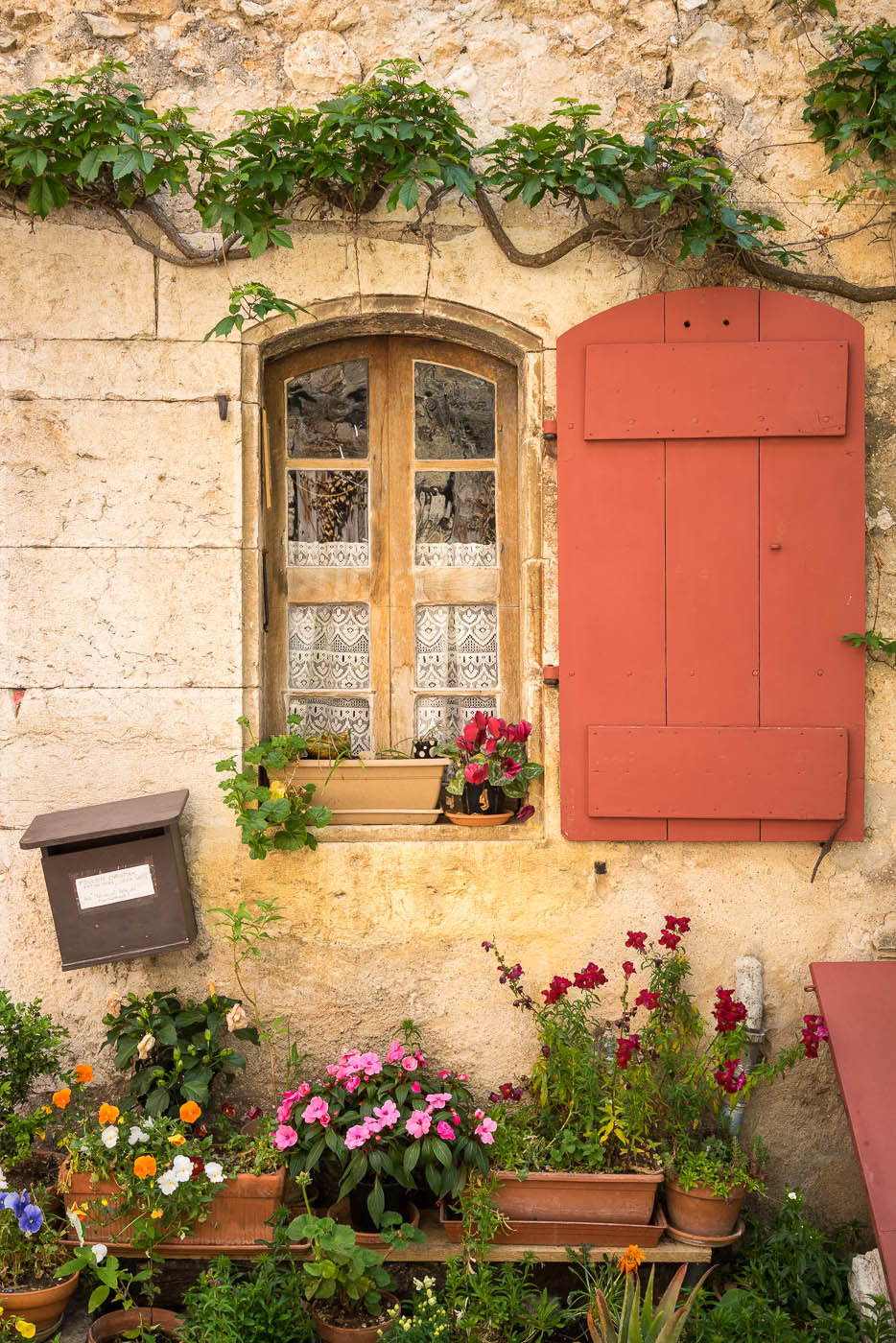 A dangling wooden mailbox on a very beautiful stone wall with flowers in Provence