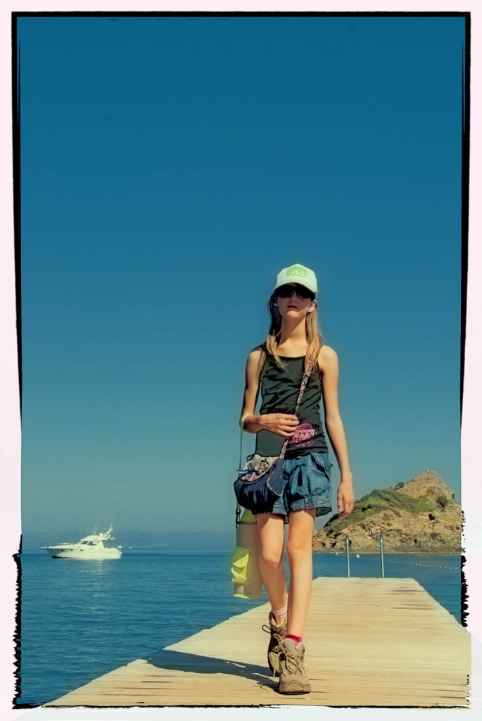 A young girl walking on a wooden quay in the mediterranean