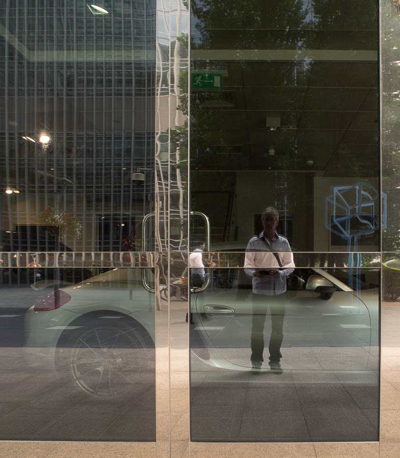A self portrait using the reflection on a Porsche shop window in Canary Wharf, London