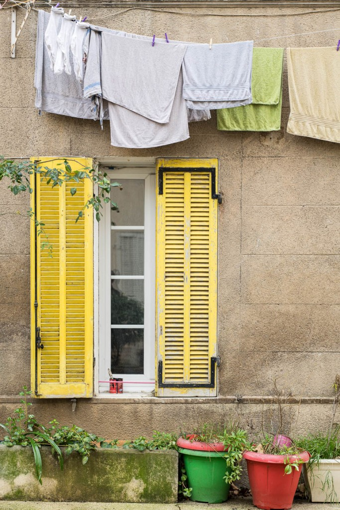 Laundry hanging over the yellow shutters of a Provence window. SOny A7r, OTUS 85/1.4