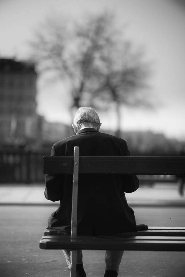A man reading on a bench near Notre Dame, in Paris. Sony A7r & Zeiss OTUS 85