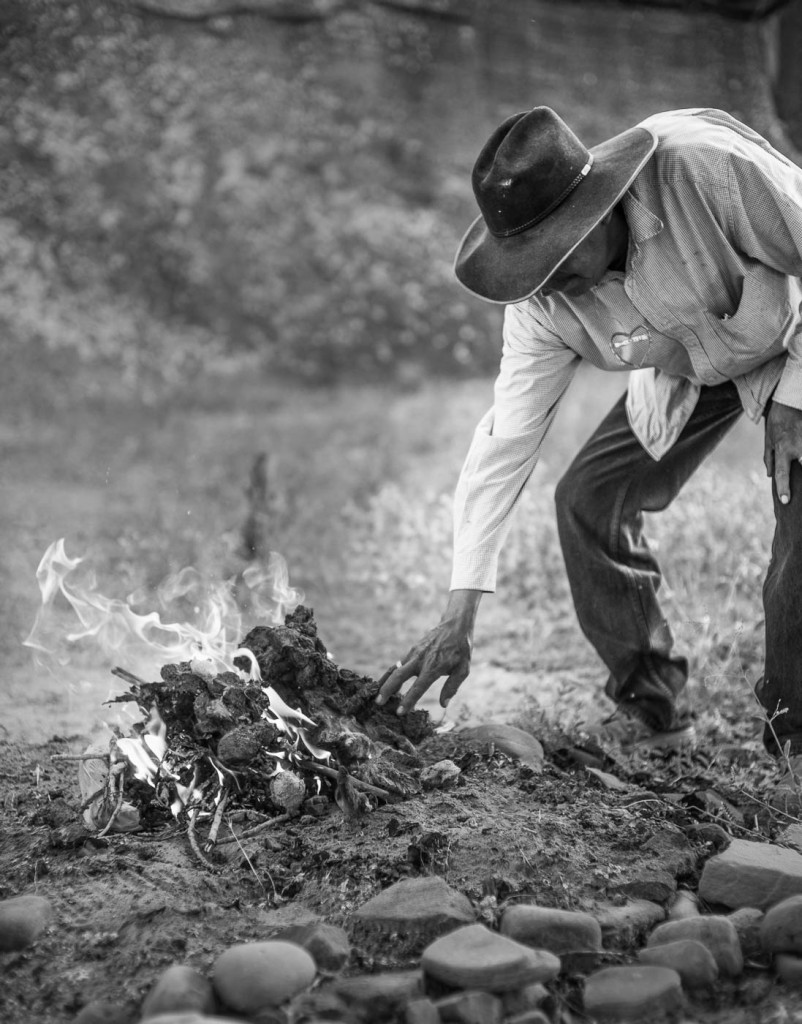 A Navajo guide places horse manure on a campfire in Canyon de Chelly