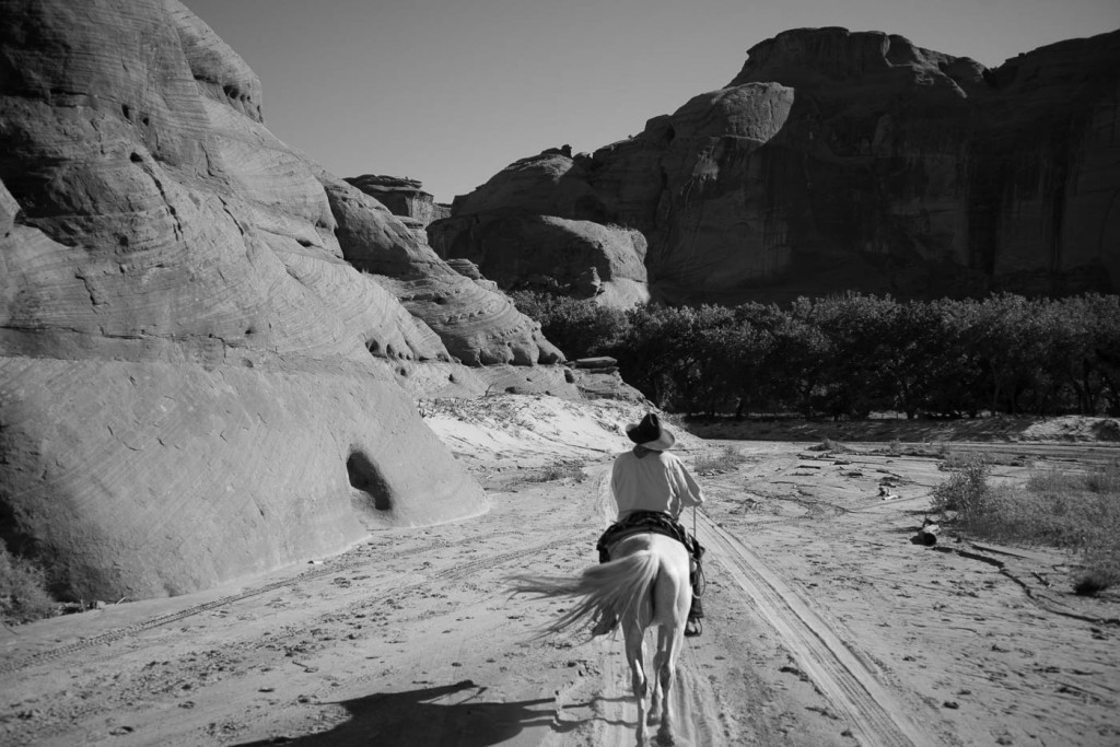 A Navajo guide on horse back on a photo tour inside Canyon de Chelly