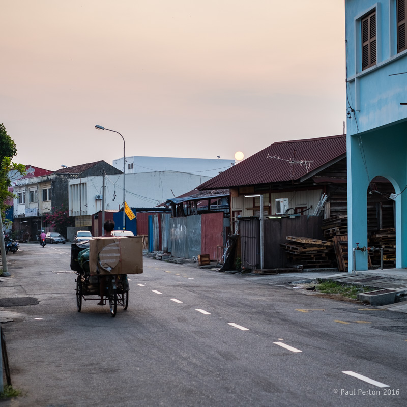 Rising sun, recycling collector - Penang. X-Pro2 with 35mm f2 @ f2.8, ISO 200. The city is full of people making a tiny income from collecting paper, plastic and glass for recycling - this chap was clearly up and out long before the sun. Processed using Thomas Fitzgerald's Velvia plug in.