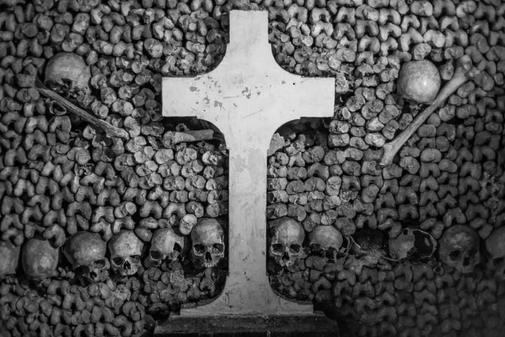 Skulls, bones and cross in Paris catacombs